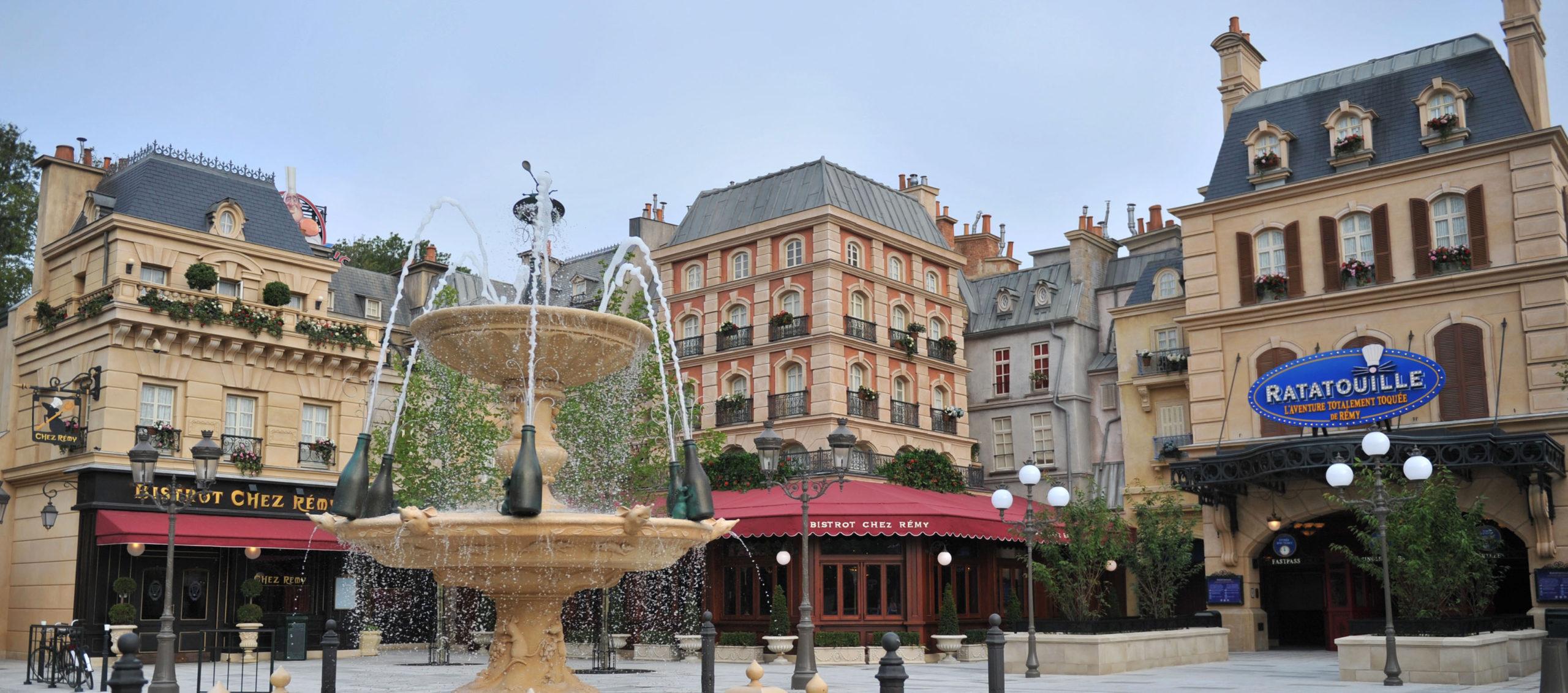 Vue de la place de Rémy avec, en premier plan, une fontaine où l'eau sort de bouteilles de champagne.