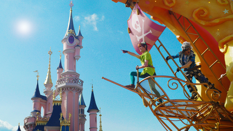 Devant le Château de la Belle au Bois Dormant, Peter Pan pointe le ciel.