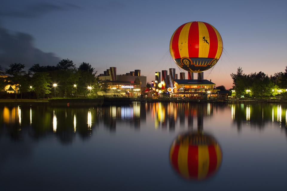 De l'autre côté du Lac Disney se dessine la rue du Disney Village. Au premier plan, la montgolfière Panoramagic prépare son envol.