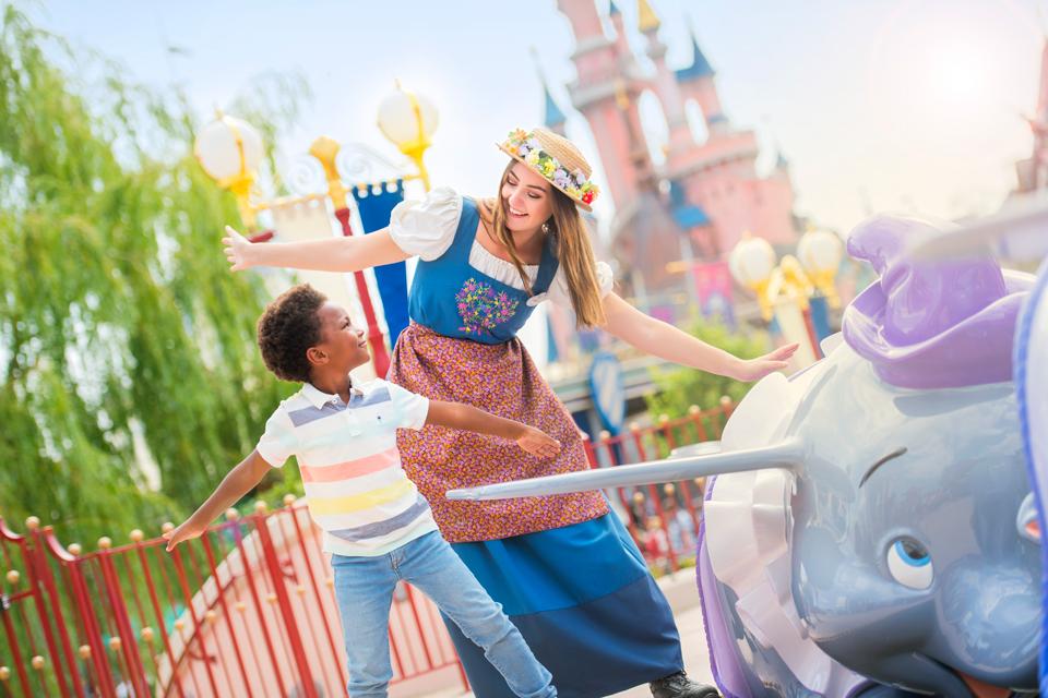 Une Cast Member joue avec un enfant à côté de Dumbo The Flying Elephant. On voit le Château de la Belle au Bois Dormant en fond.