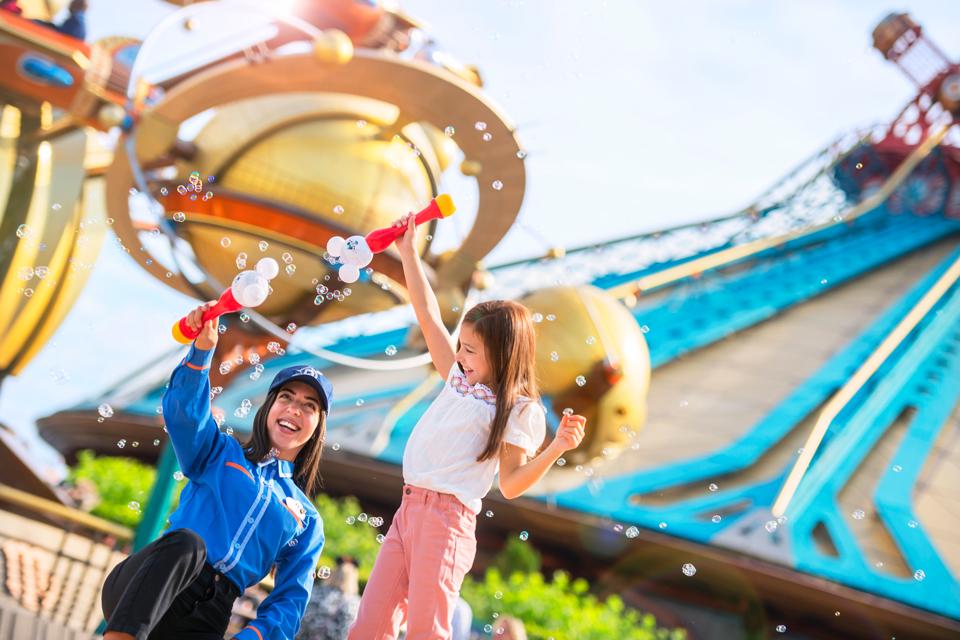 Une Cast Member et une jeune fille s'amusent avec des bulles devant Orbitron et Space Mountain.