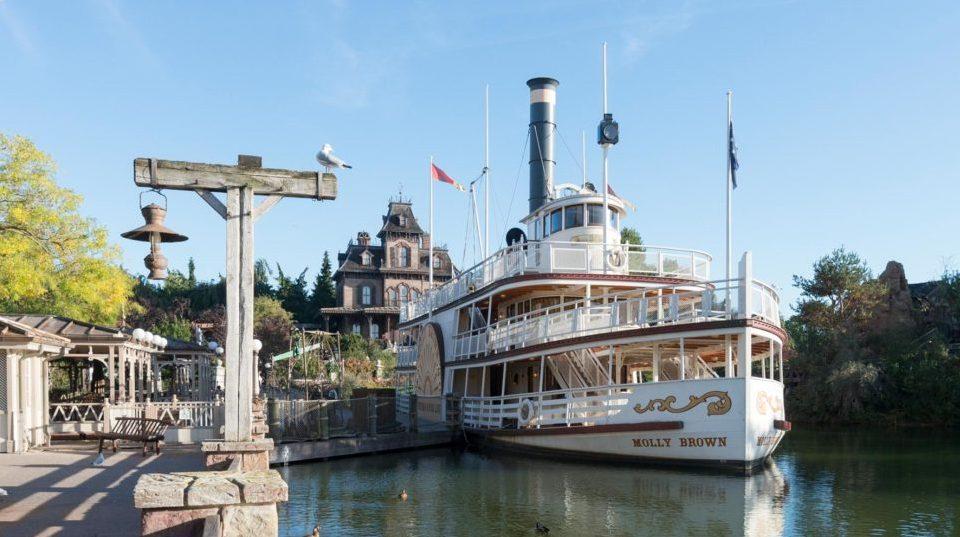 Une vue panoramique des Rivers of America, avec le bateau à roues à aube Molly Brown, et Phantom Manor et Big Thunder Mountain en fond.