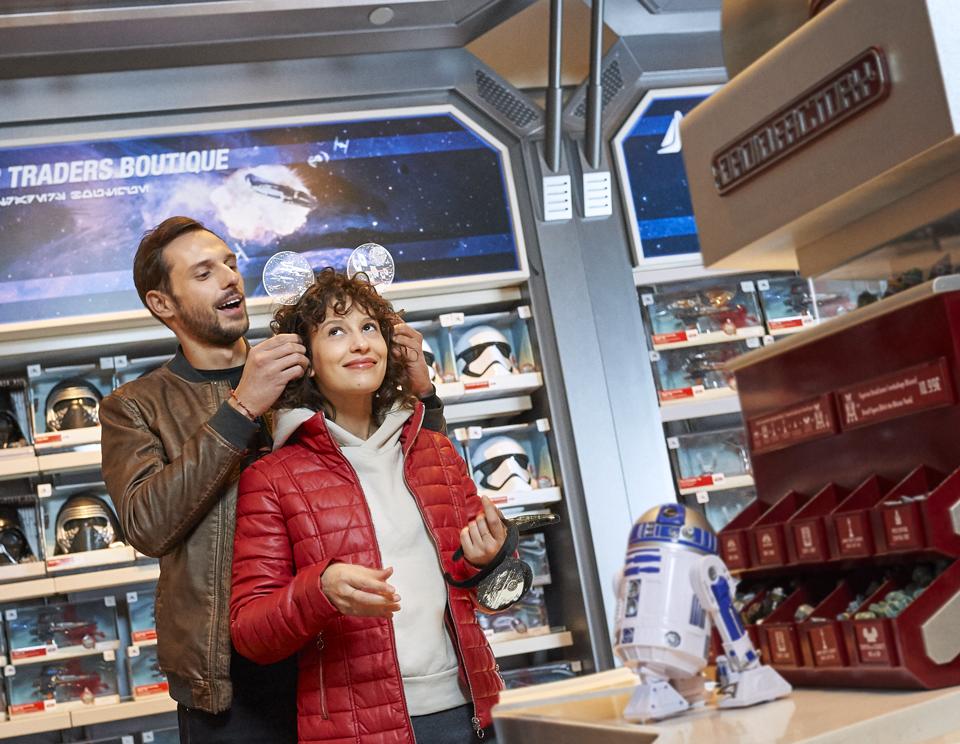 Un homme pose sur la tête d'une femme des oreilles de Mickey sur le thème de Star Wars à l'intérieur de la boutique Star Traders.