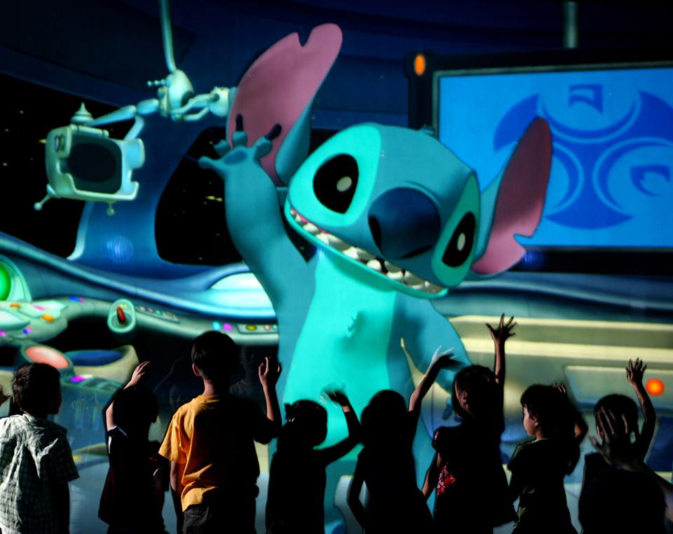 Des enfants, de dos, font un signe à Stitch qui leur répond.