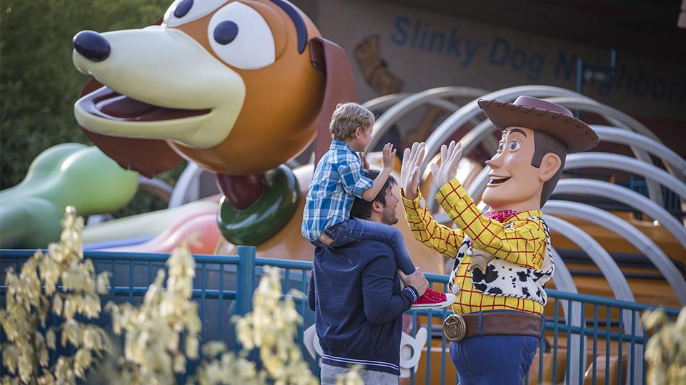Un enfant, sur les épaules de son père, tape dans les mains de Woody, devant Slinky Dog Zigzag Spin.