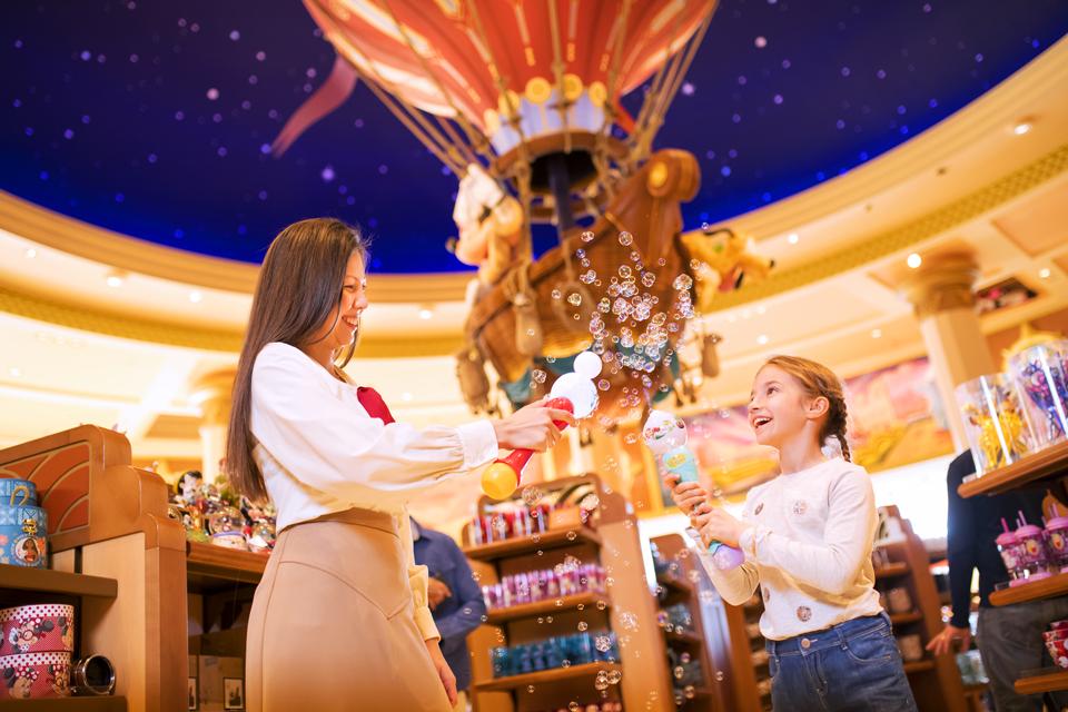 Une petite fille fait des bulles de savon avec une Cast Member dans la boutique World of Disney.