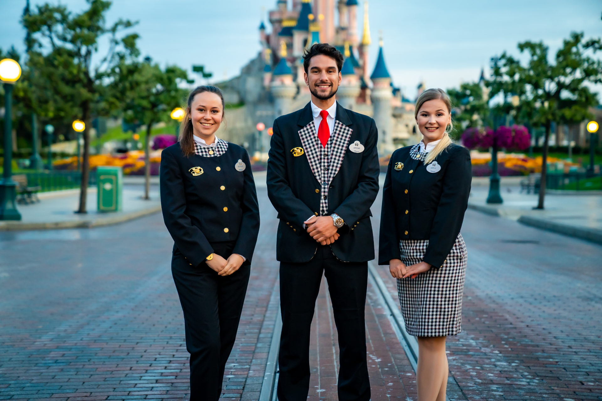 Three Cast Members in front of the Sleeping Beauty Castle